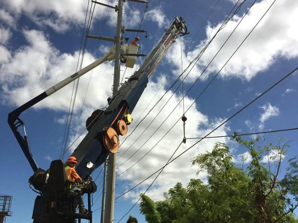 A power line is lifted by work crews who are restoring Puerto Rico's electric power grid.