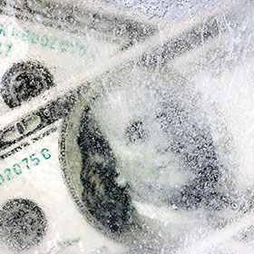 Photograph of money behind a layer of ice.