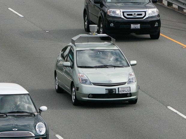 An autonomous Prius driving on a highway with other cars.