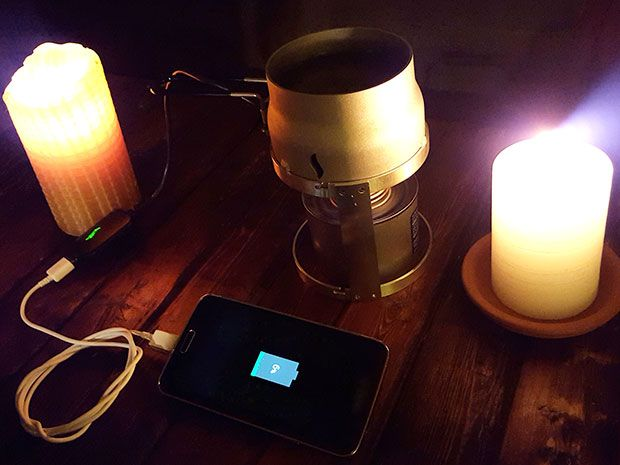 Two candles, a sterno can, and a smartphone connected to a charging device.