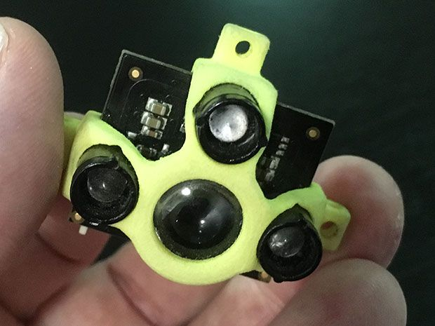 Fingers hold a small circuit board which supports four cylinders with lenses. A yellow/green piece of plastic partially covers the circuit board.