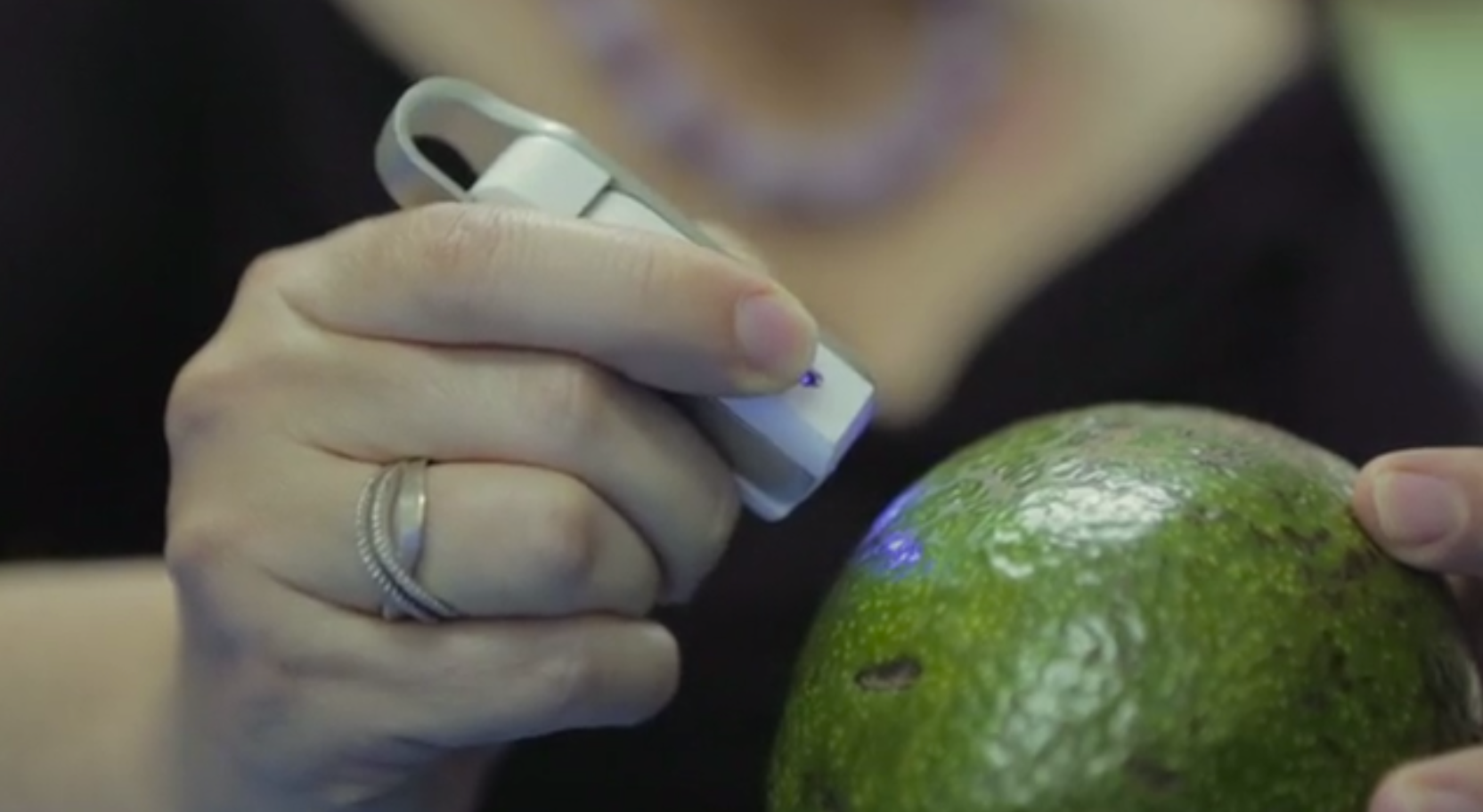 A handheld spectroscopy tool called the SCiO shines a blue light on an avocado to check its molecular composition.
