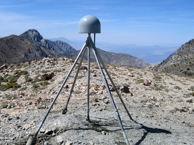 A silvery tripod on dry ground.