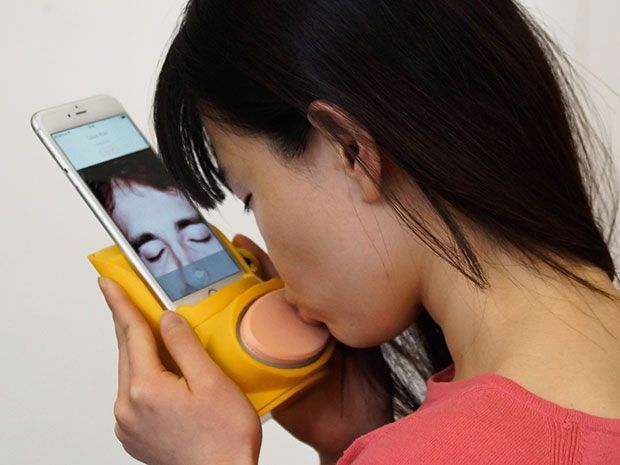 A woman kisses a plastic pad attached to her smartphone to send a virtual kiss to the person she's video chatting with.