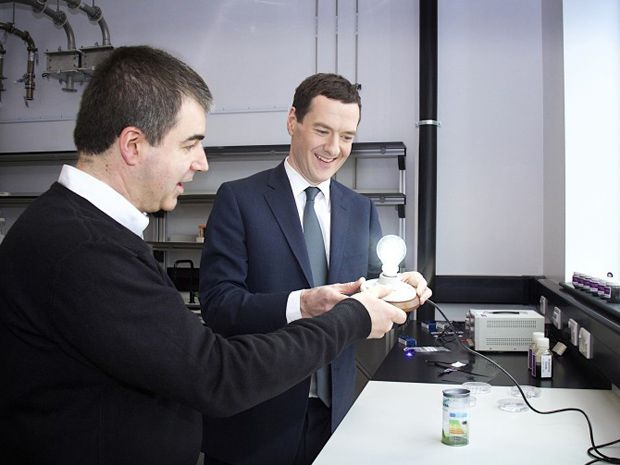 Two men in a laboratory gaze at an illuminated lightbulb mounted in a fixture they are holding in their hands
