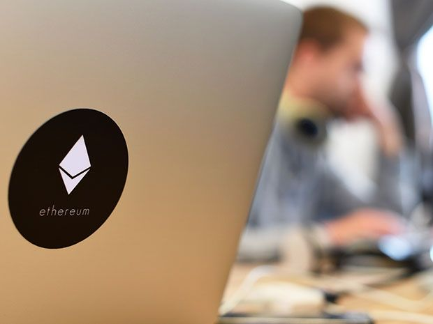 Symbol of Ethereum on the back of an open laptop. Ethereum uses blockchain technology to build virtual companies and other services.