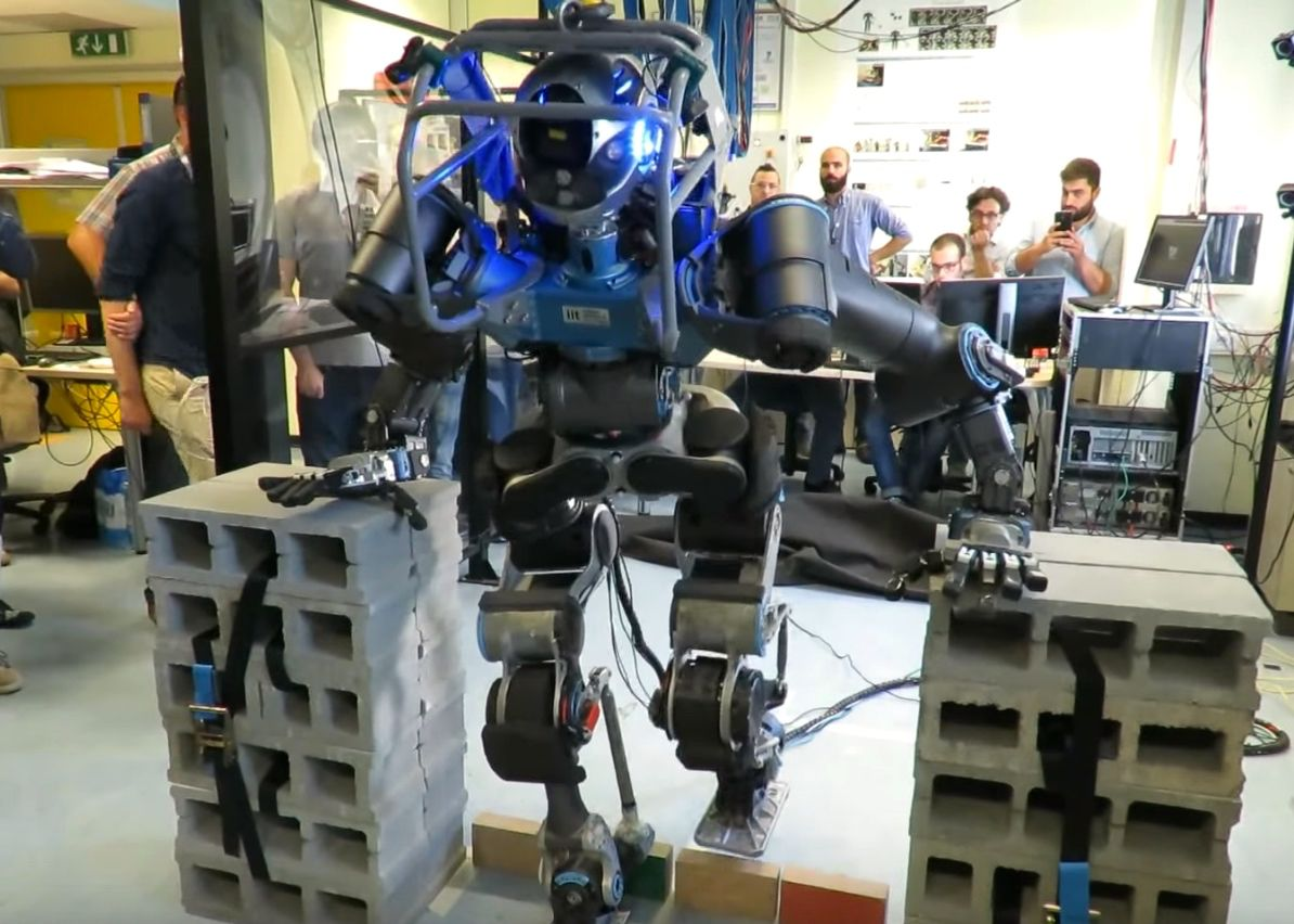 WALK-MAN humanoid robot steps over an obstacle during a demonstration.
