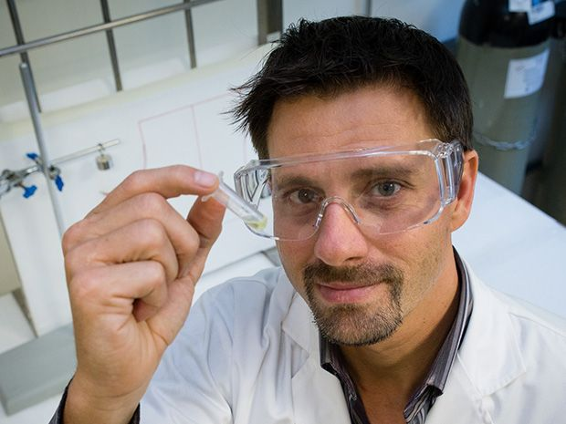 A man with a goatee wearing a white lab coat and safety glasses holds up a small vial filled with a yellow-green liquid.