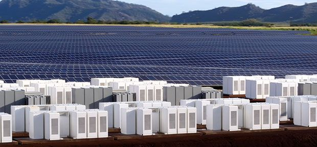 Lithium-ion energy storage units stand in front of an array of solar photovoltaic panels in Hawaii.