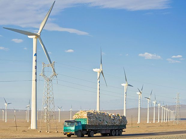 A truck drives past a wind farm in Xinjiang, China.