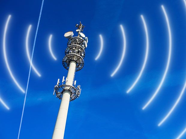 A silver tower lined with antennas against a clear blue sky broadcasts cellular signals.