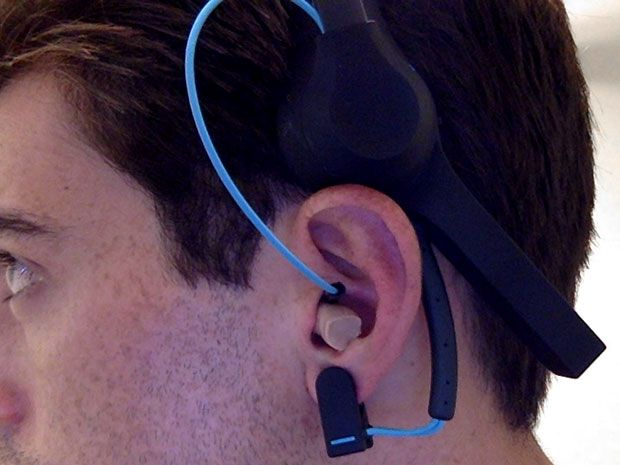 Man wearing an earplug-like device that's connected by a wire to a headset