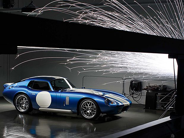 A blue and white sports car with sparks flying in front of it.