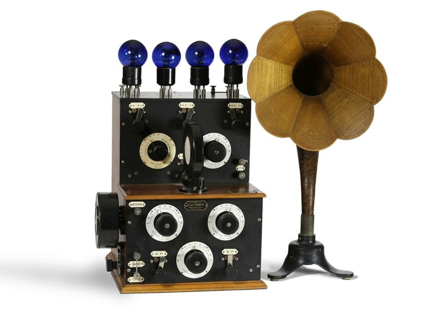 "ANOTHER ""PIANO"" RADIO: Another exceptionally beautiful, though not terribly compact, home radio setup is the French ""Piano"" 4–valve receiver, shown here with Grammont Radiofoto type 209 marine lamps and a ""Le Parfait"" loudspeaker, made in about 1925."