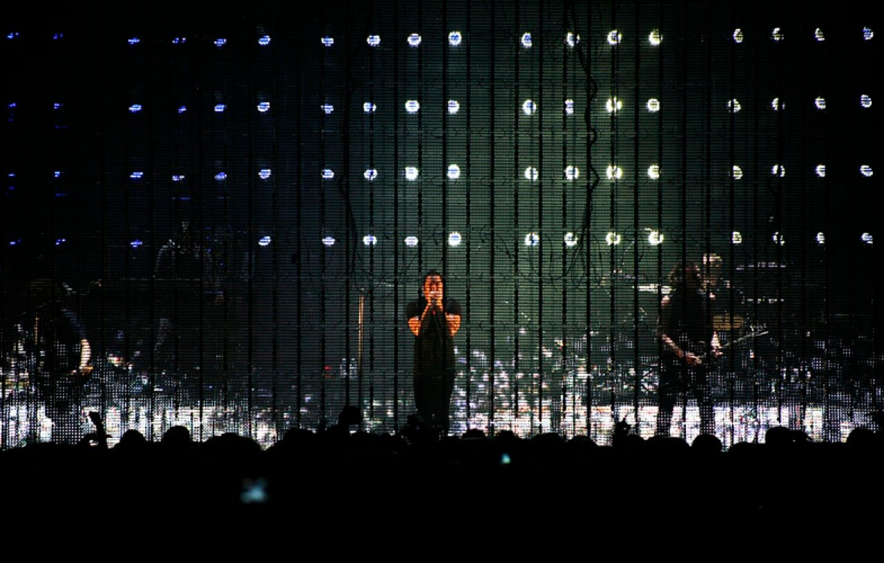 CAGED ON STAGE: As the band plays behind the stealth screen, the lights are sometimes left unlit to achieve a cagelike effect.<
