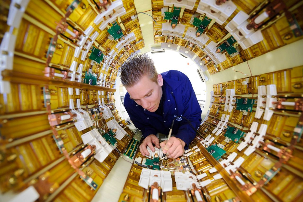 If you've ever had an MRI scan, you've surely wondered what was going on inside that claustrophobia-inducing tube. Here, an engineer adjusts some of the coils and other electronics that produce the magnetic field and RF energy behind the highly detailed images.