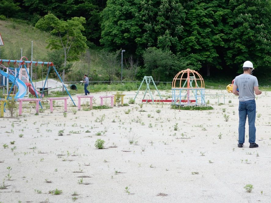 <b>A Place to Play?:</b> The government has prioritized the decontamination of Fukushima's schools, and several centimeters of topsoil were removed from this school playground. The Safecast volunteers checked the government's post-cleanup radiation report with their own equipment. They found that radiation levels were low in the playground, but they increased significantly in the easily accessible woods just beyond.