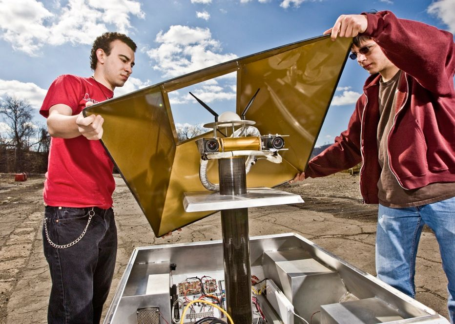 UNDER THE HOOD: Field-test engineers Charlie Munoz [left] and Ethan Minogue remove the rover's main cover to inspect its electronics. The current prototype uses mostly off-the-shelf hardware, including a PC-based system to control its two mast-mounted cameras. <