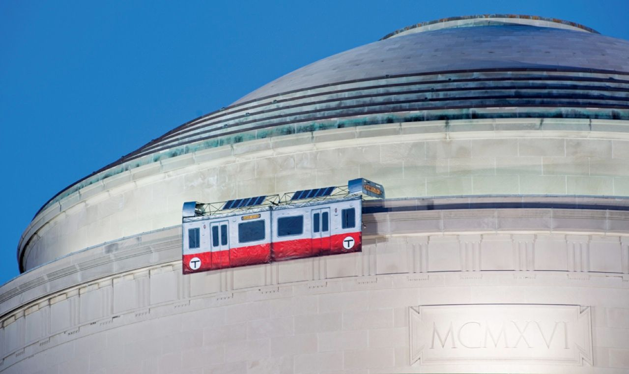 "Among the many objects to grace the roof of MIT's Great Dome, a.k.a. Building 10, are a replica of the Apollo 11 moon landing, an actual campus police car, a working telephone booth, and [pictured] a pair of solar-powered subway ""cars"" that used the dome itself as a track to shuttle back and forth."