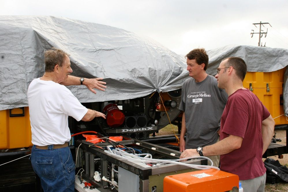 Ernest Frank [left] of Southwest Research Institute, discusses how to fix an oil leak in the robot's sampling arm with John Spear [middle], a microbiologist at the Colorado School of Mines, and David Wettergreen, who led the software effort at Carnegie Mellon. When the robot is operating, the sampling arm extends out from the body about 2 meters and gathers solid and liquid specimens from the sinkhole.