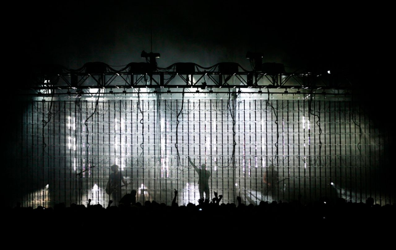 "PEEK-A-BAND: Nine Inch Nails performs in shadows behind the front stealth screen. The idea was to be able to ""see through screens,"" as Reznor puts it, and create something ""we could afford to take out.""<"