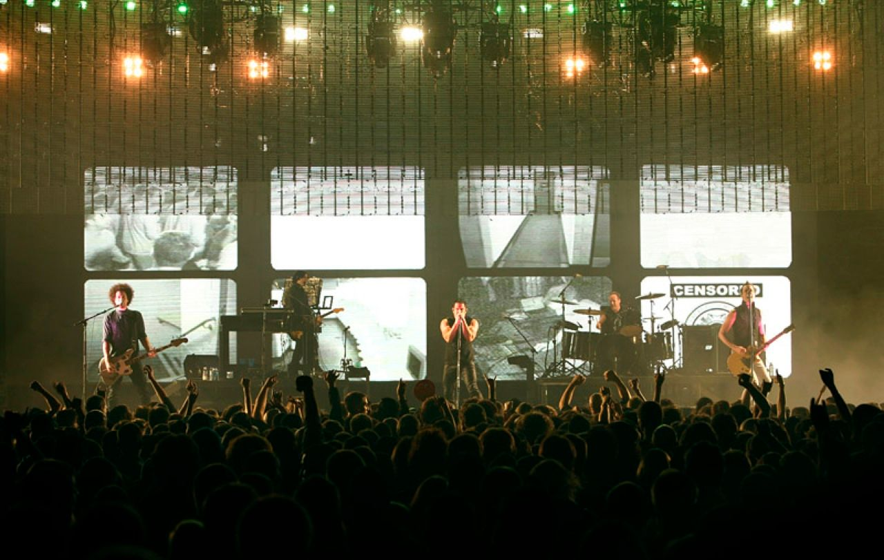 "ROCK GOD, LED GEEK: Trent Reznor [center at microphone] of Nine Inch Nails performs live during his 2008 ""Lights in the Sky"" tour. Video screens behind the band show surveillance camera footage of the venue. <"