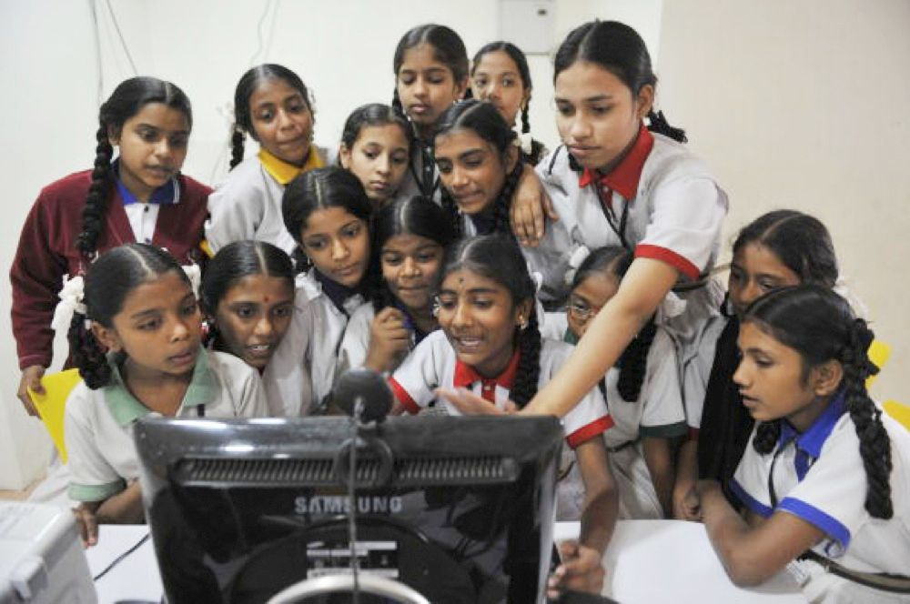 "This group of students at a high school in Hyderabad, India, have congregated around a computer monitor for an interactive lesson with a ""Skype granny,"" one of a group of British retirees who, via the Internet, share their knowledge with impoverished children who don't have access to a full complement of teachers where they live."
