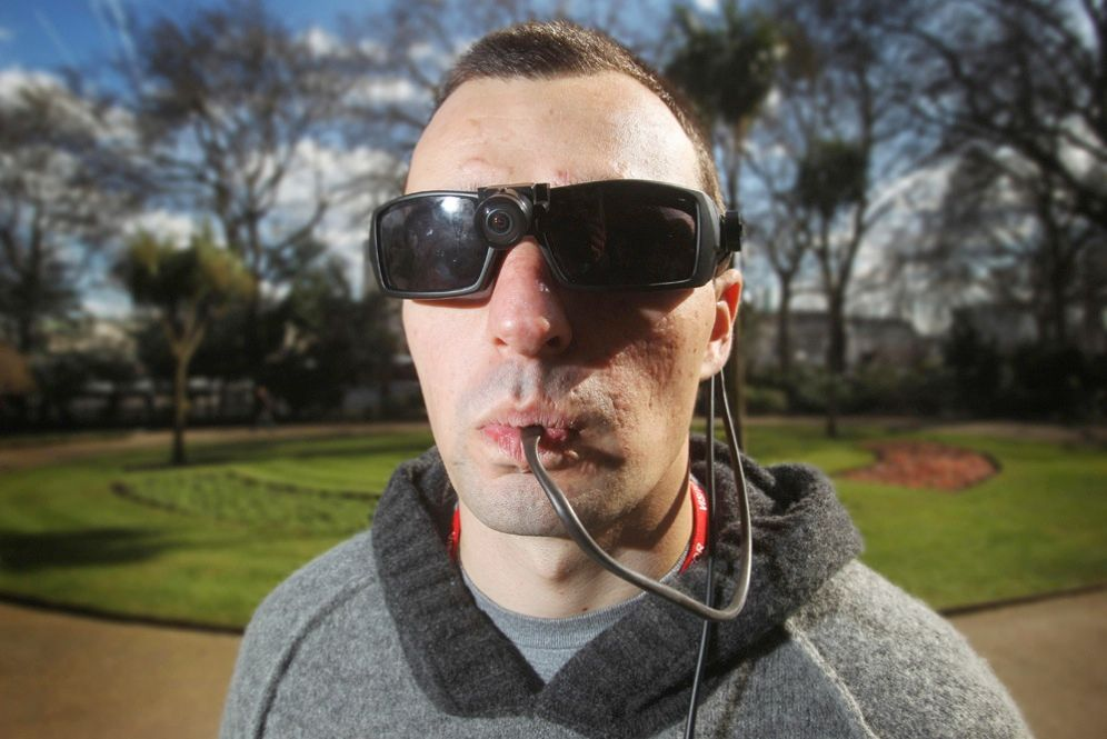 "No, this isn't a novelty drinking device for campers or stadium-goers. The cable is part of a system that allows the man, a former British soldier who lost his sight to a grenade blast, to ""see"" with his tongue. Images captured by a camera attached to the glasses are transformed to signals that create impulses on a pad inserted in his mouth."