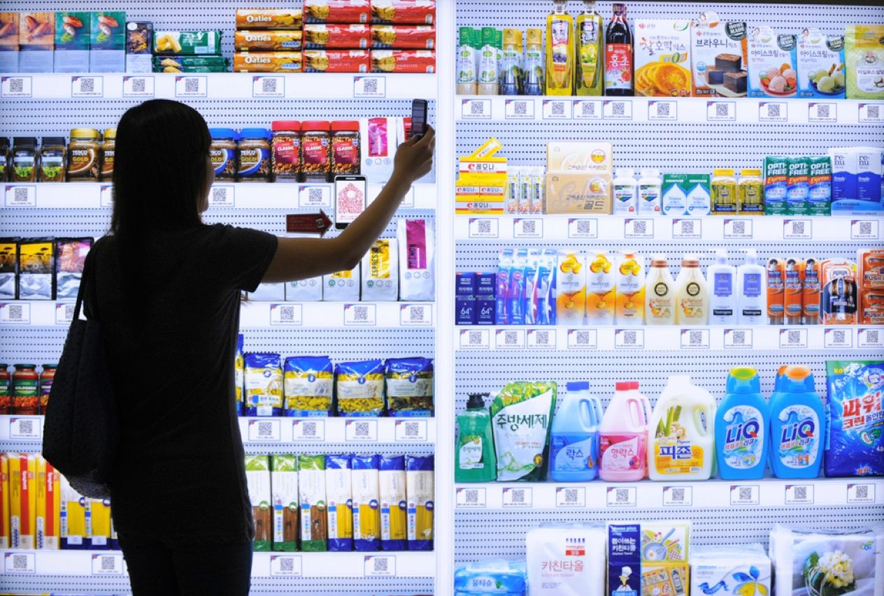 Tesco Home Plus, the giant grocery chain, has created the world's first virtual store, whose products line the walls of a subway station in Seoul, South Korea. As this woman uses her smartphone to scan the Quick Response codes for the goods she wants, the items pop up in an online shopping cart. After the purchase is complete, the order will be delivered right to her door.