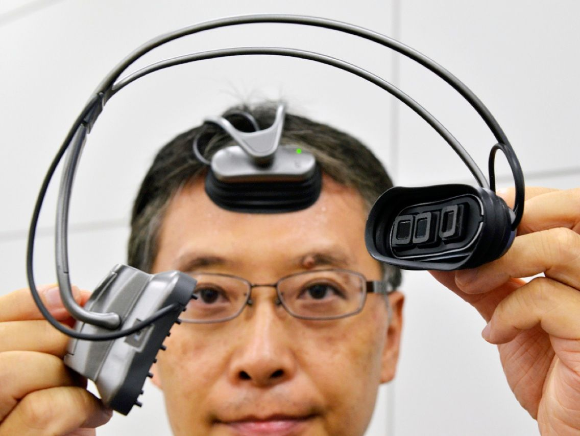 An engineer at Hitachi shows off a portable brain-machine interface that uses an optical sensor to detect changes in blood flow in the prefrontal cortex. Researchers at the electronics firm and at Japan's Tohoku University developed the neuroimaging device with the aim of giving people the ability to control electronic gadgets with their thoughts. The researchers expect a commercial version to be available within five years.