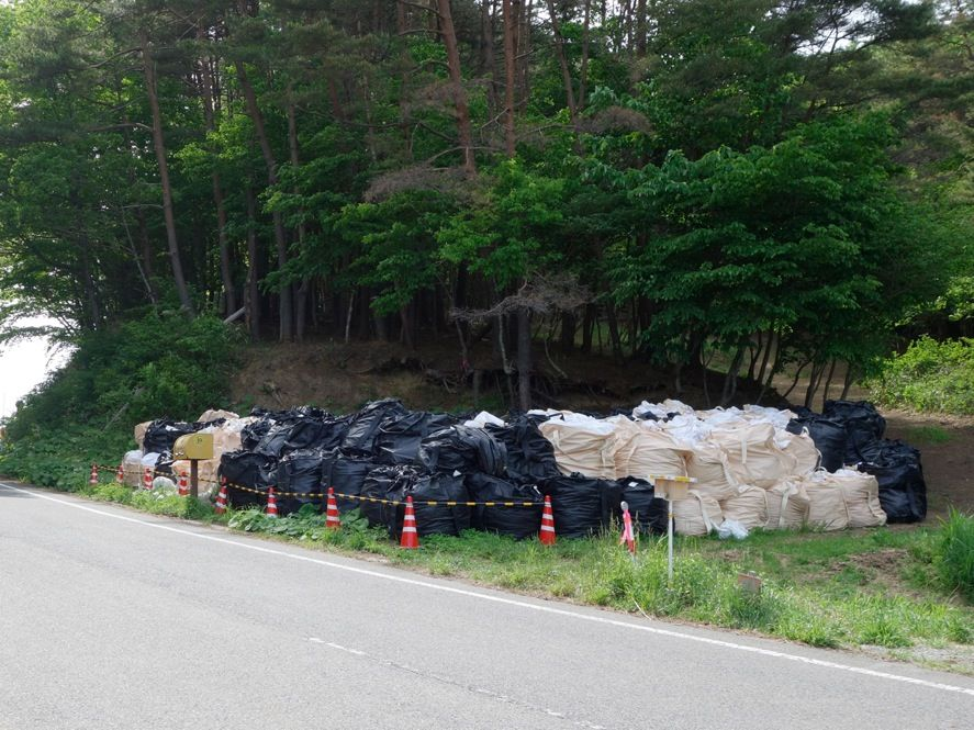 <b>Taking Out the Trash:</b> Many roadside areas in the evacuation zone have been decontaminated, but it's impossible to scrape the top layer of soil from all of Fukushima's hills. Even the limited cleanup poses big storage problems. Bags of contaminated dirt are a common sight along the roads of Fukushima, as the government is still trying to decide on a long-term storage solution.