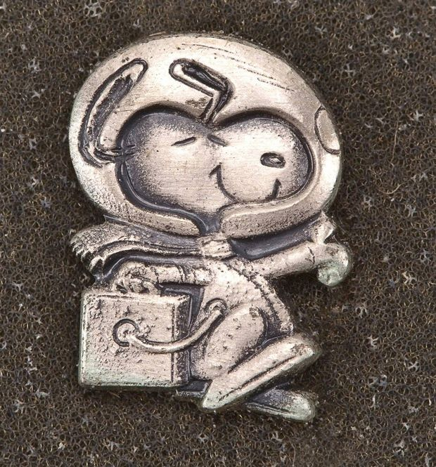 """This lapel pin, which sold for $5185, flew on Apollo 13 and comes from astronaut Fred Haise's collection. Snoopy was adopted as NASA's """"manned flight awareness"""" mascot to get kids and the public interested. Apollo crews took the pins with them into space, then gave them to members of the ground crew who exemplified exceptional support. Receiving a Snoopy pin was considered a high honor."""