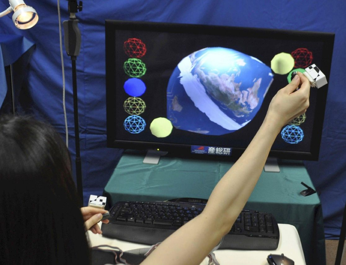 Japan's National Institute of Advanced Industrial Science and Technology has developed an interactive 3-D TV. As the woman demonstrating the device touches the image of Earth projected in the air in front of her, the virtual globe deforms, as if it were a balloon being pulled at one end.