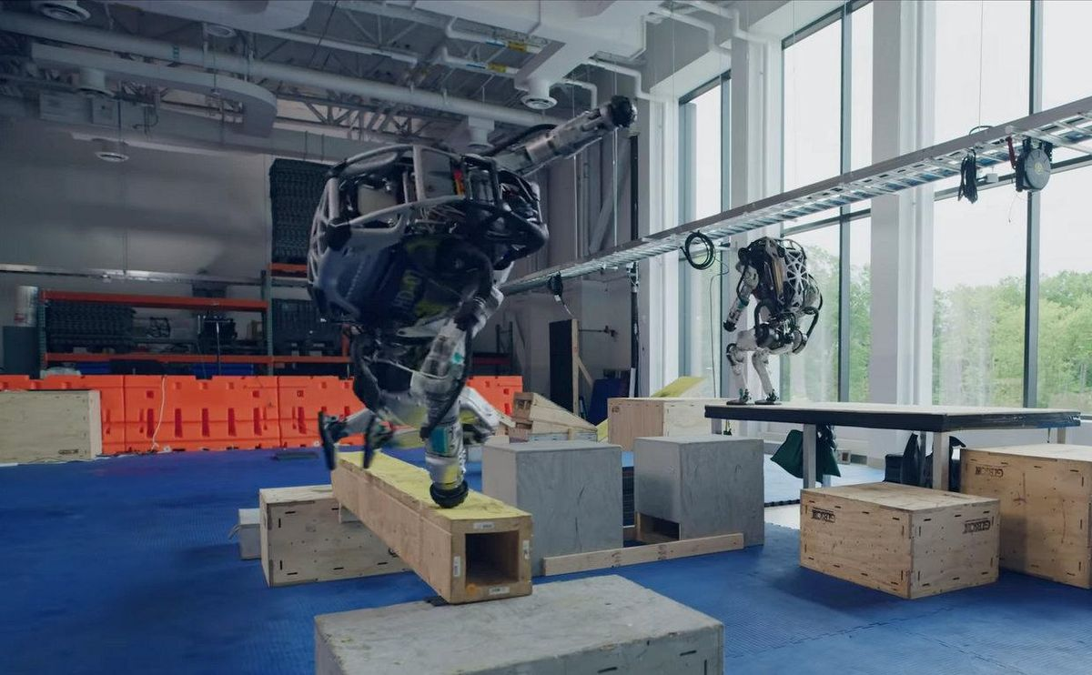 Two bulky humanoid robots clamber over an indoor obstacle course