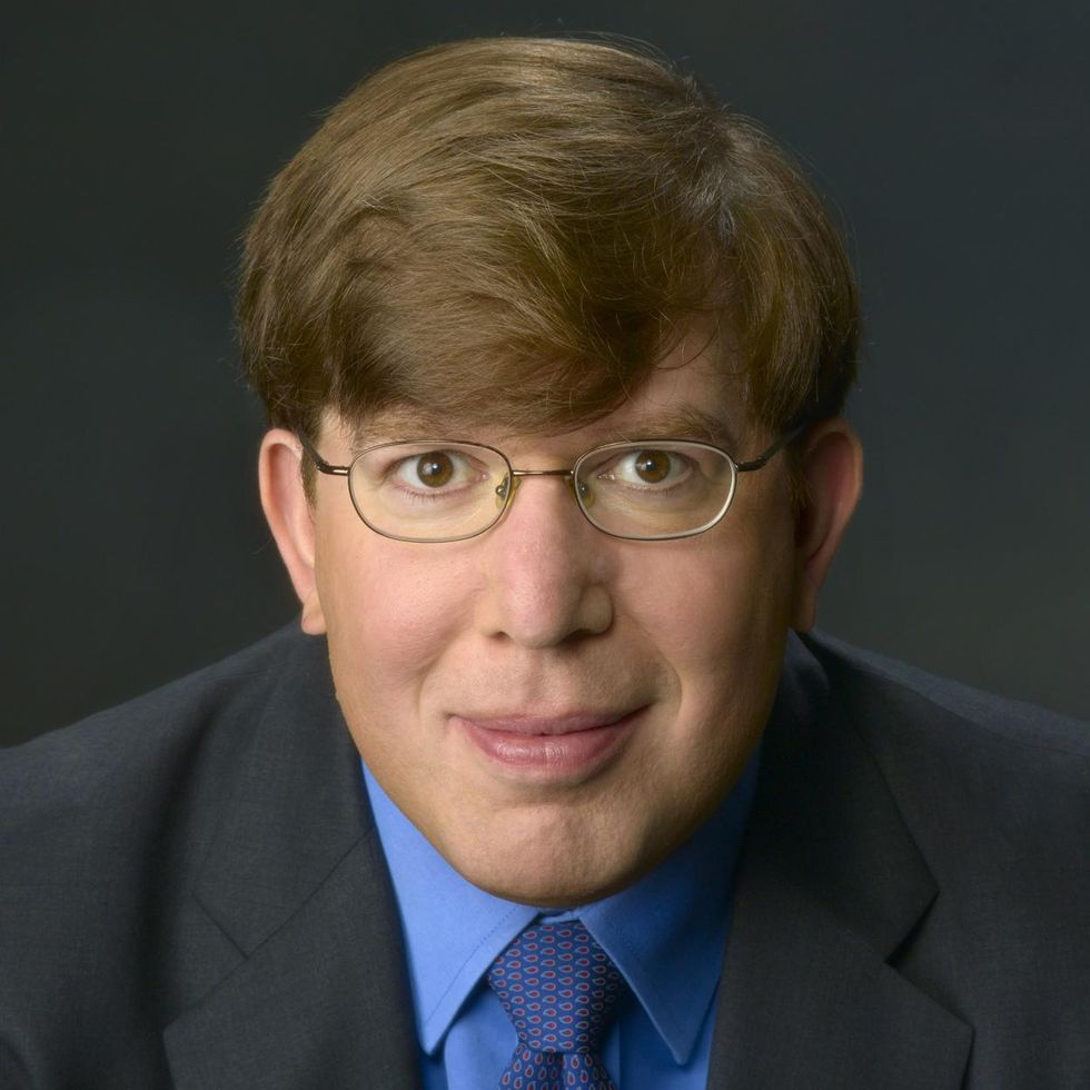 Closeup of a man wearing glasses and a suit