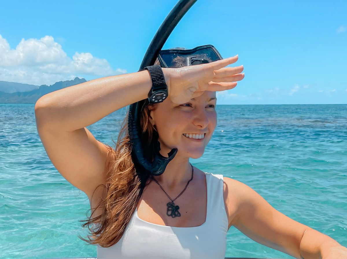 In the foreground, a woman in a white bathing suit and snorkel gear holds up her arm, which has a watch-like device on the wrist. Blue skies and water in the background.