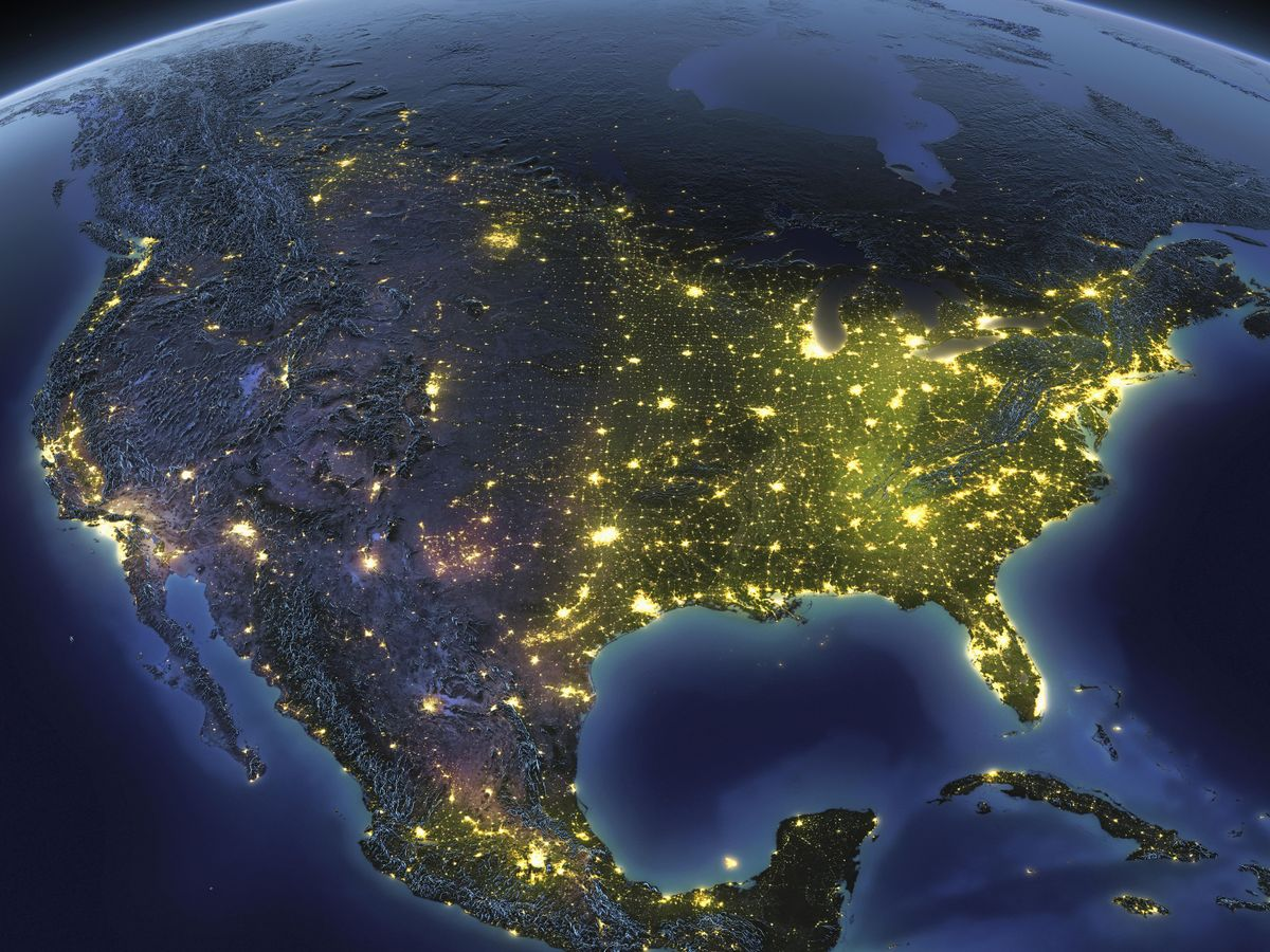 Satellite overhead view of the United States at night. The land mass is grey with bright yellow lights across the country.