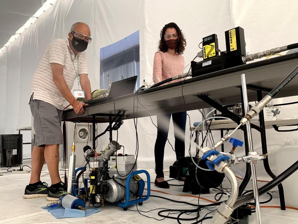 A man and a woman wearing masks stand at a table in a white tent. In the foreground is silver and blue equipment including a nozzle from which white spray is emitting.