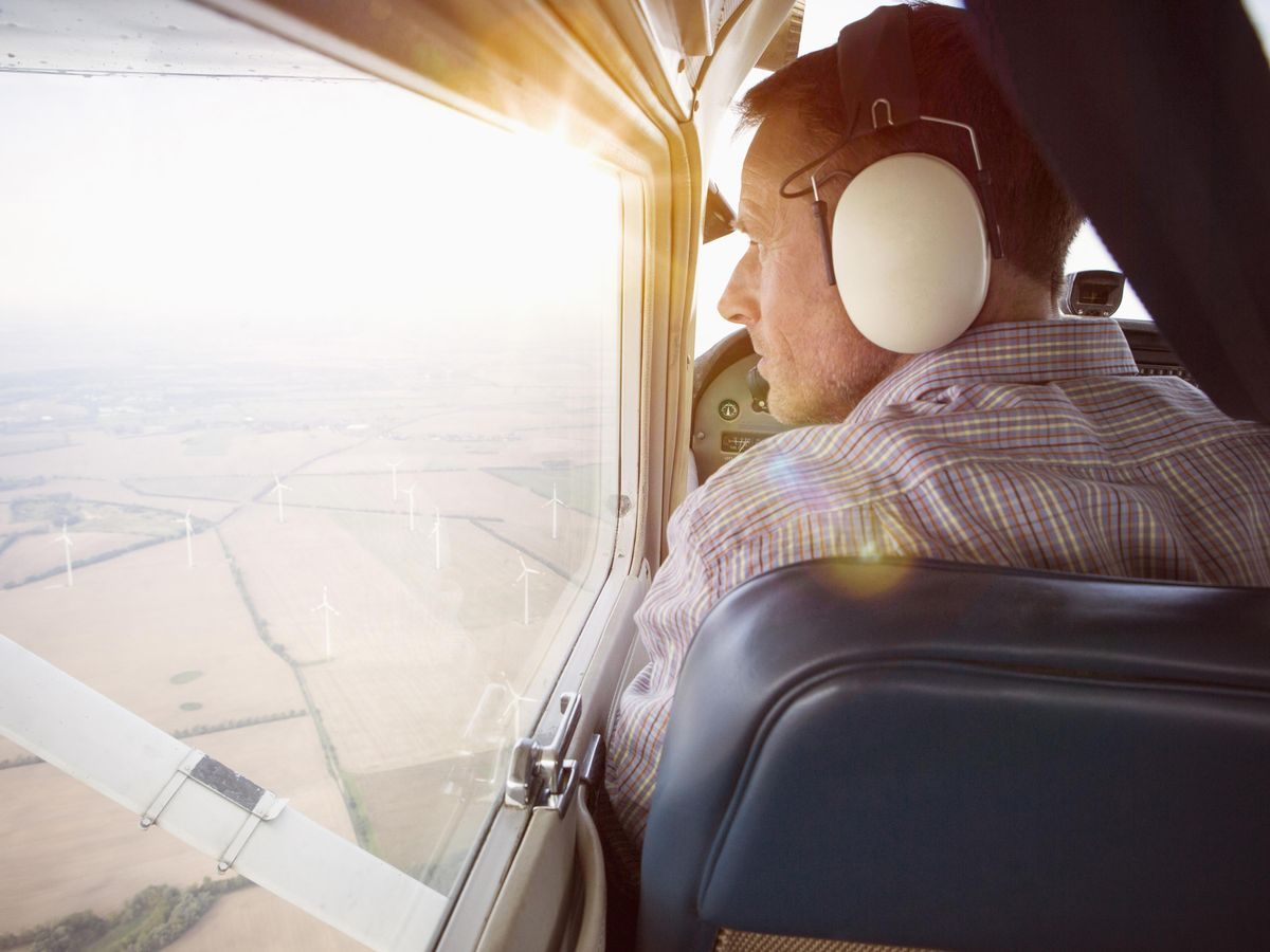 Rear view of a man with headphones looking out of the window from a private plane. Below is an aerial view of land