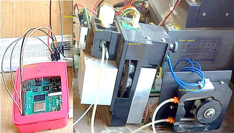 A pink box with a green circuit board and electronics is connected by wires to a assortment of electronics including a power supply and pump.