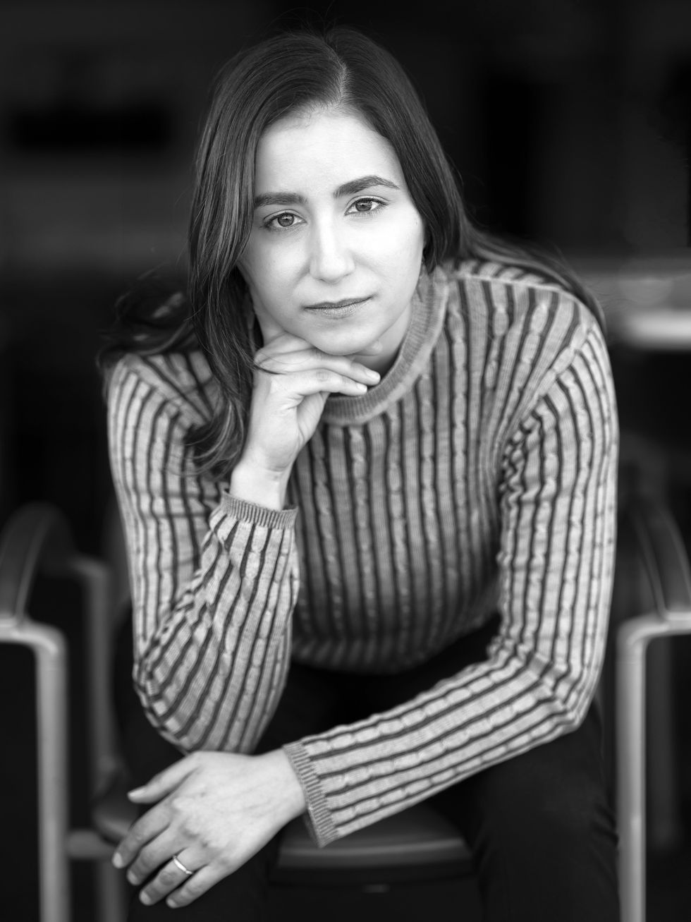black and white photo of a woman with dark hair and a striped shirt