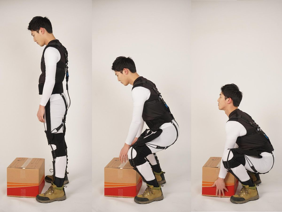 # images showing a person bending down to pick up a box while wearing the exosuit.