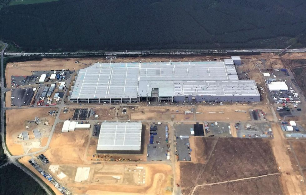 Aerial photo shows a very large grey rectangular roof of a factory. There is a smaller square roofed building in the foreground, and parking lots with vehicles on the left, right and foreground.