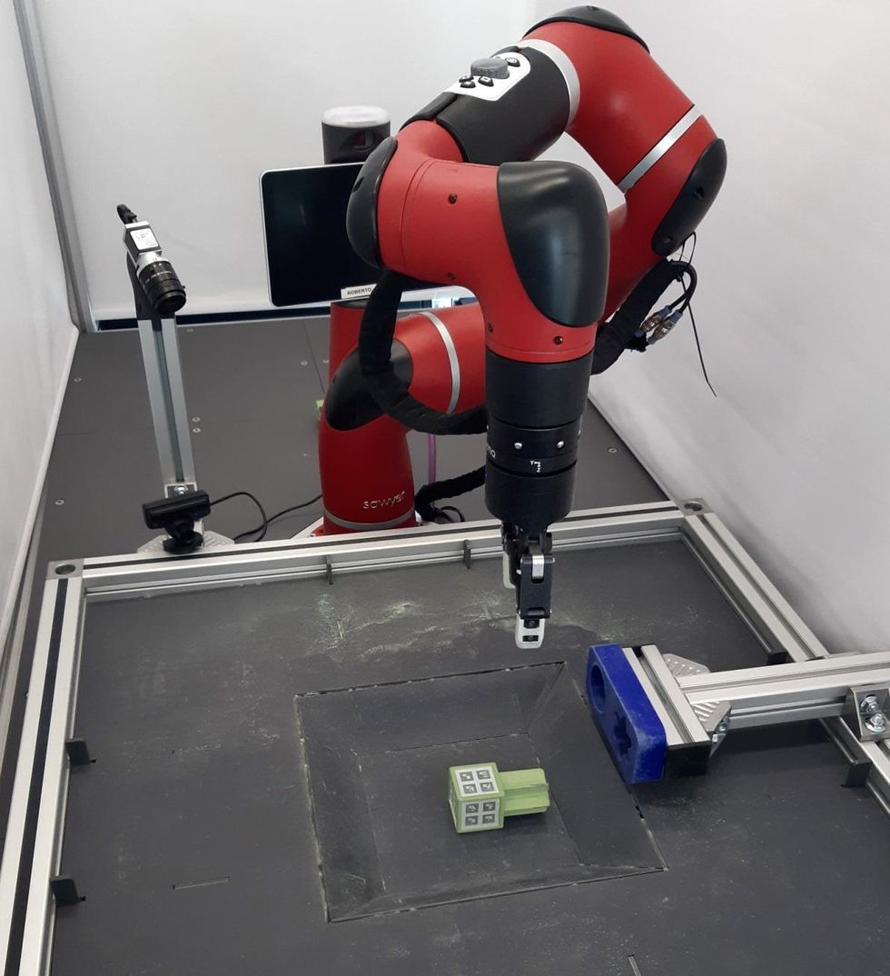 Image of a robot pushing a star-shaped peg into a hole in a box.
