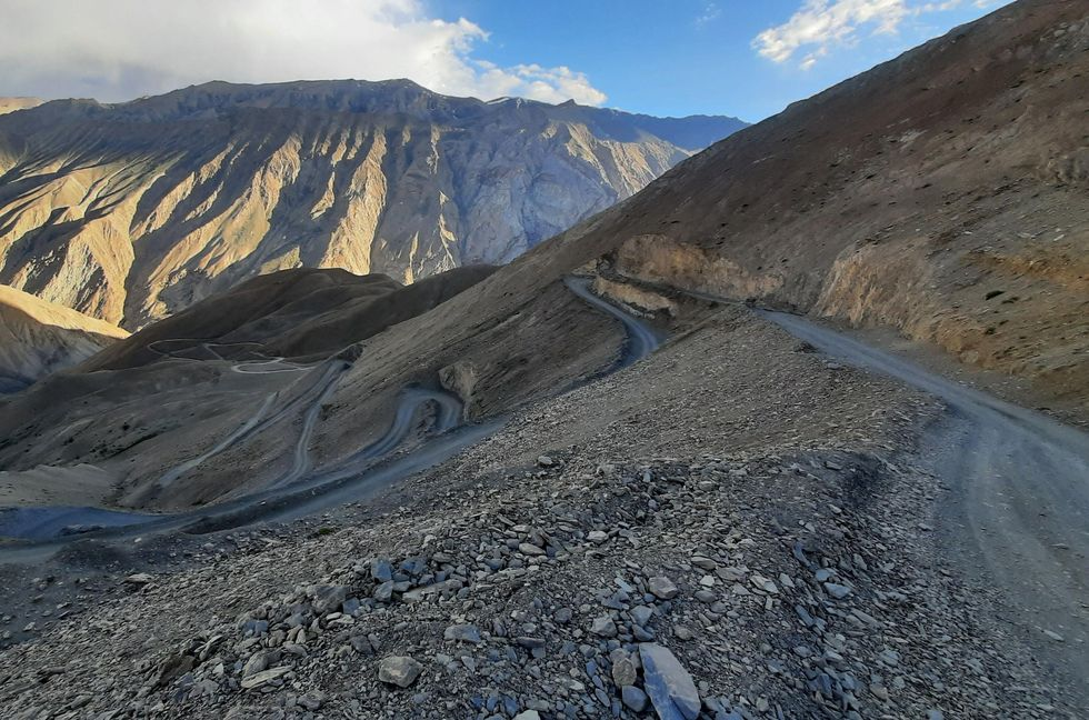 An unpaved road winds through a mountain. Blue skies and clouds in the background.