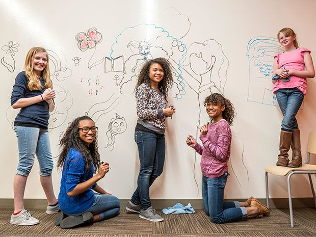 Five teen girls express themselves on a whiteboard wall, mixing art with engineering could attract girls like this to STEM careers