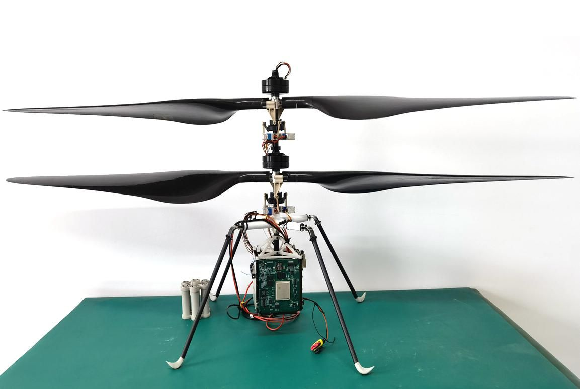 Four thin raised black legs join in an x. A vertical piece with equipment and wires is on top, and hanging under is a circuit board. The top of the base has two wide black propellers extending out.