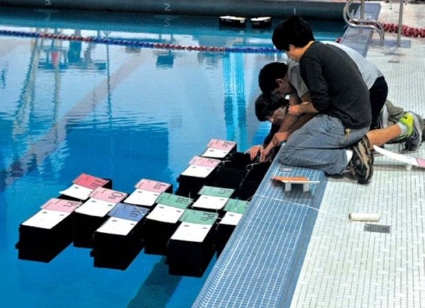 Groups of modular robotic boats form structures on water.