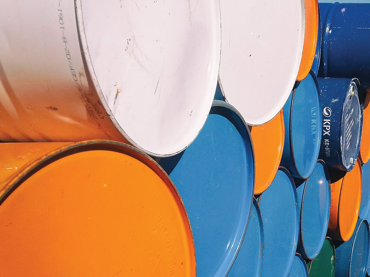 Horizontally stacked colored oil cans.