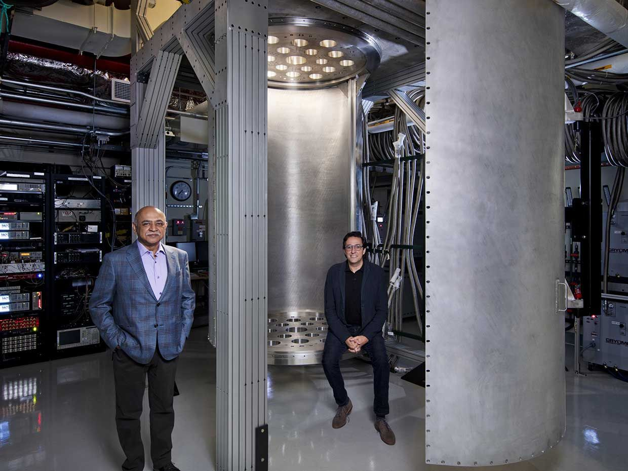 """IBM CEO Arvind Krishna (left) and Director of IBM Research Dario Gil are pictured with a 10-foot-tall and 6-foot-wide """"super-fridge,"""" a custom built dilution refrigerator larger than any commercially available."""